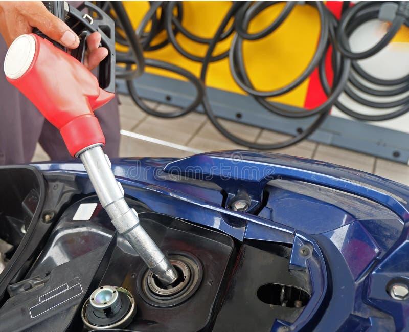 De olieautomaat vult de motorfiets, Energieconcept opnieuw royalty-vrije stock afbeelding
