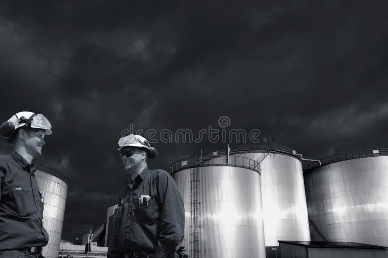 De olieindustrie, arbeiders en donkere stormachtige wolken stock afbeeldingen