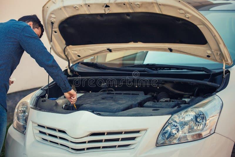 De olieniveau van de bestuurderscontrole in de motor van een auto, die onder zijn autokap kijken voor het veilig drijven en een o royalty-vrije stock foto's