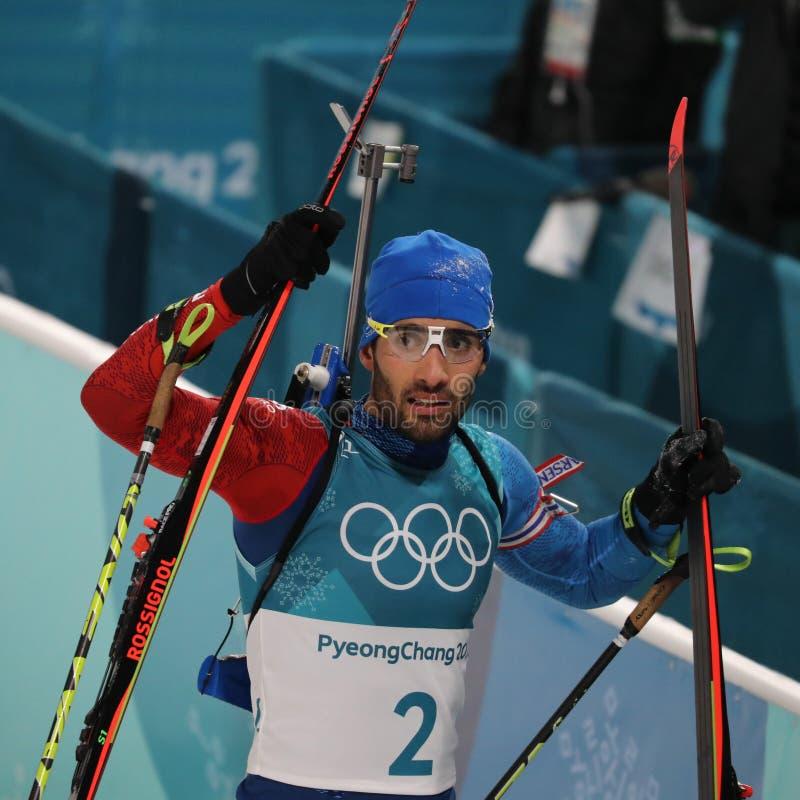 De olympische kampioen Martin Fourcade van Frankrijk viert overwinning in de massabegin van biathlonmensen ` s 15km bij 2018 de W stock foto