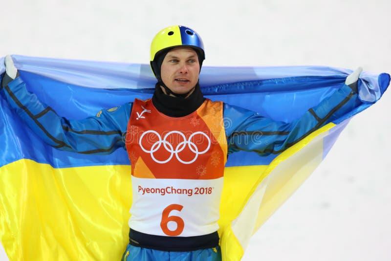 De olympische kampioen Oleksandr Abramenko van de Oekraïne viert overwinning in het Vrije slag van Mensen` s Antennes Ski?end bij stock afbeelding