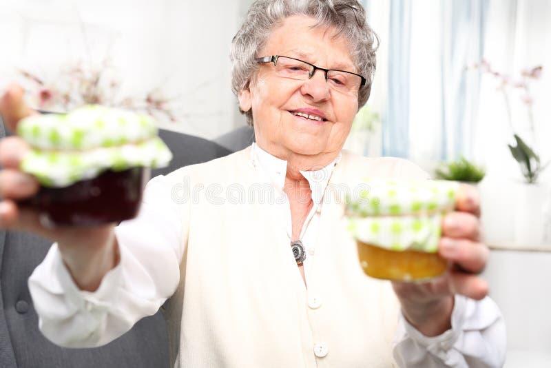De oma bereidt komfitury in kruiken voor stock afbeeldingen