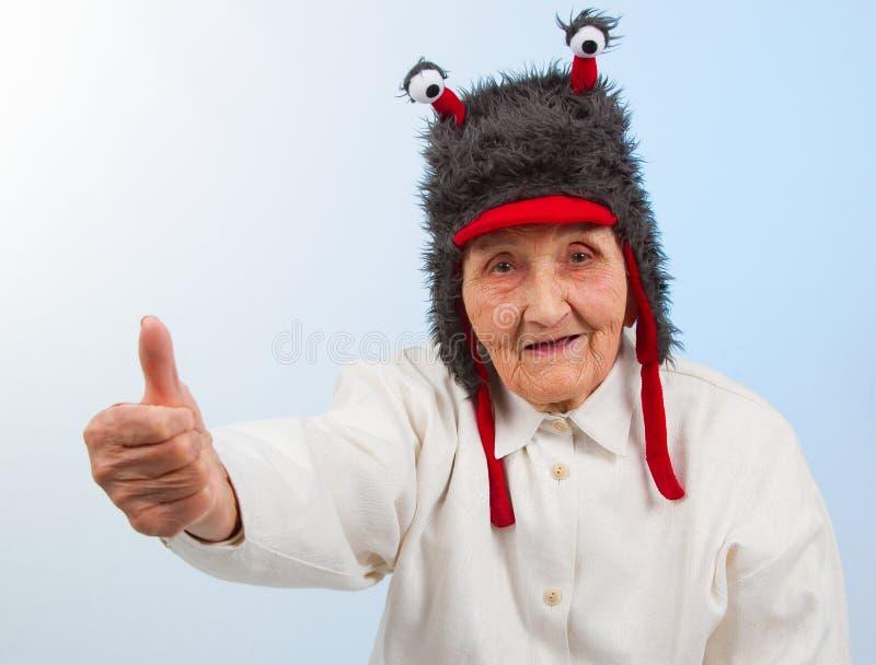 De oma in grappige hoed toont duimen royalty-vrije stock foto