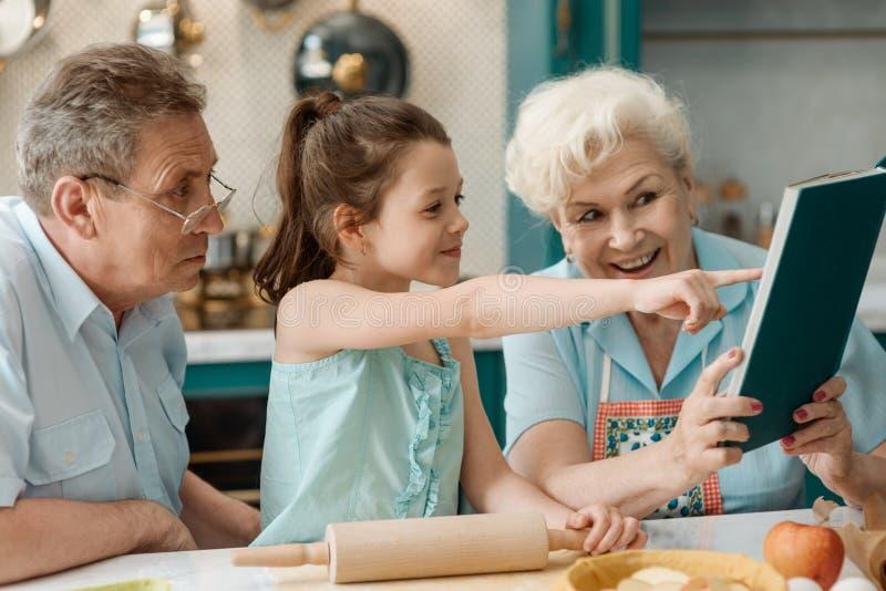 De oma onderwijst kleindochter om te bakken stock foto's