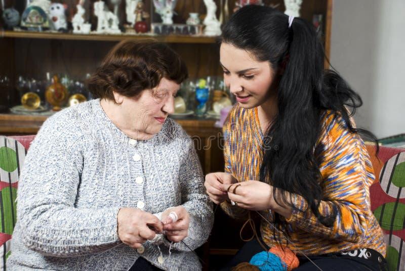De oma onderwijst kleindochter om te breien