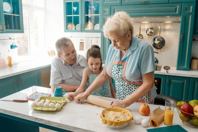 De oma onderwijst kleinkind om te bakken royalty-vrije stock foto's