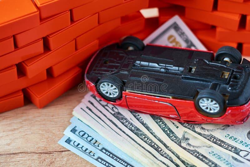 De omgekeerde auto op stapel van een dollar factureert Concept autoverzekering, schade na het ongeval stock fotografie
