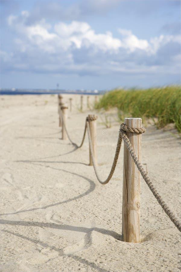 De omheining van de kabel op strand. stock afbeelding