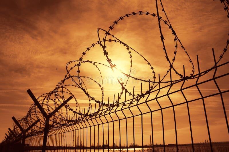 De omheining van het gevangenisprikkeldraad bij zonsondergang royalty-vrije stock afbeeldingen