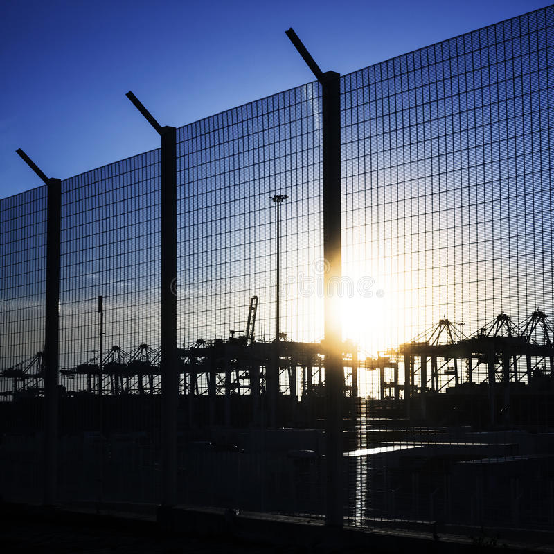 De omheining van het havengebied met silhouetten van kranen stock foto's