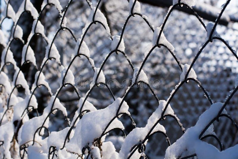 De omheining van het metaalgaas met cellen de ketting-verbinding met sneeuw wordt behandeld die stock foto