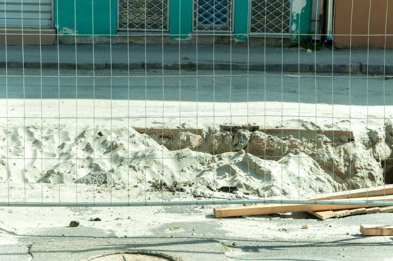 De omheining van de metaalveiligheid op de straat parallel met het geulhoogtepunt van zand na het werk van wegexscavation stock fotografie