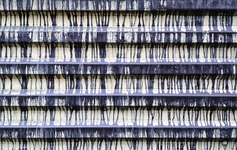 De omheining wordt gemaakt van golftin met veelvoudige vlekken van verf Textuur grunge royalty-vrije stock foto's