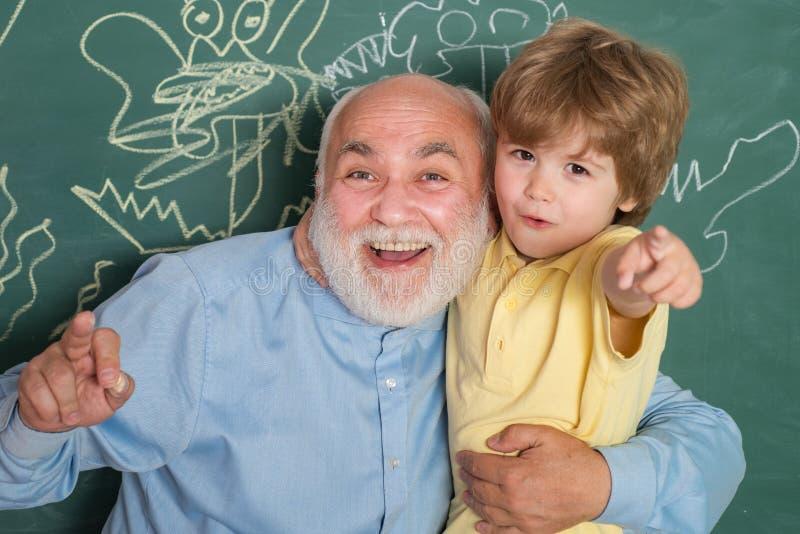 De omhelzing en omhelst Van hem geniet van sprekend aan grootvader Het leren en onderwijsconcept Vader die haar zoon in klaslokaa stock foto
