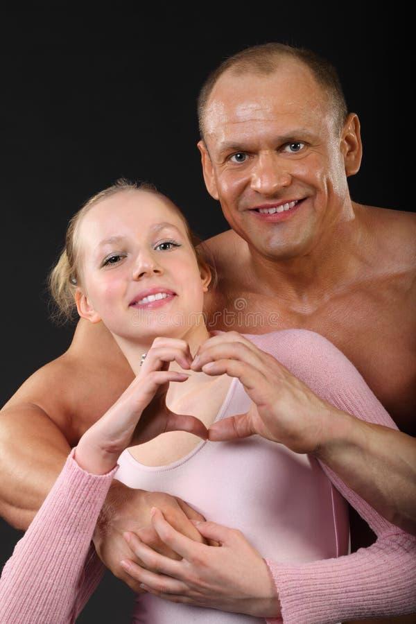 De omhelzingen van de bodybuilder met meisje royalty-vrije stock afbeeldingen
