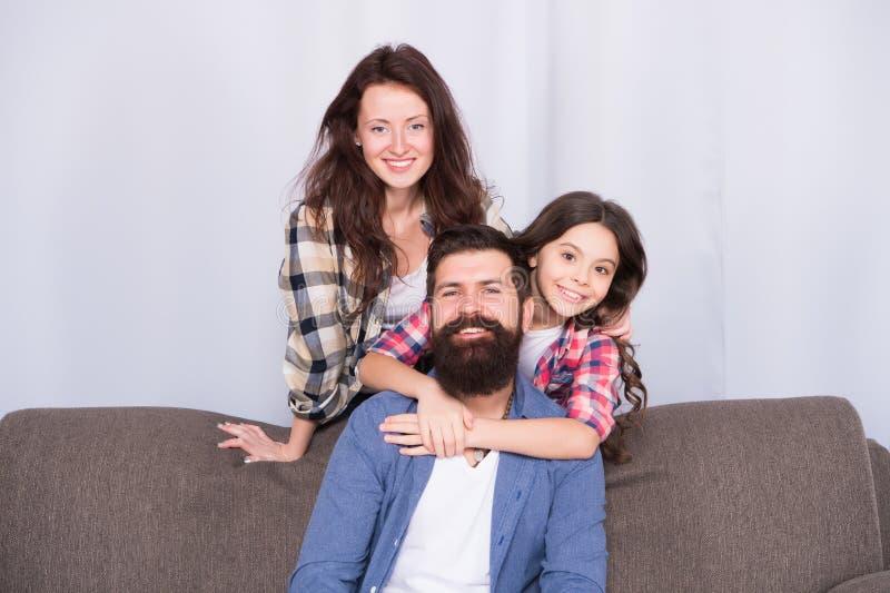 De omhelzingen zijn volledig Te retourneren Gebaarde man en vrouwenliefdedochter Vader, moeder en kind thuis Familiedag weinig royalty-vrije stock fotografie