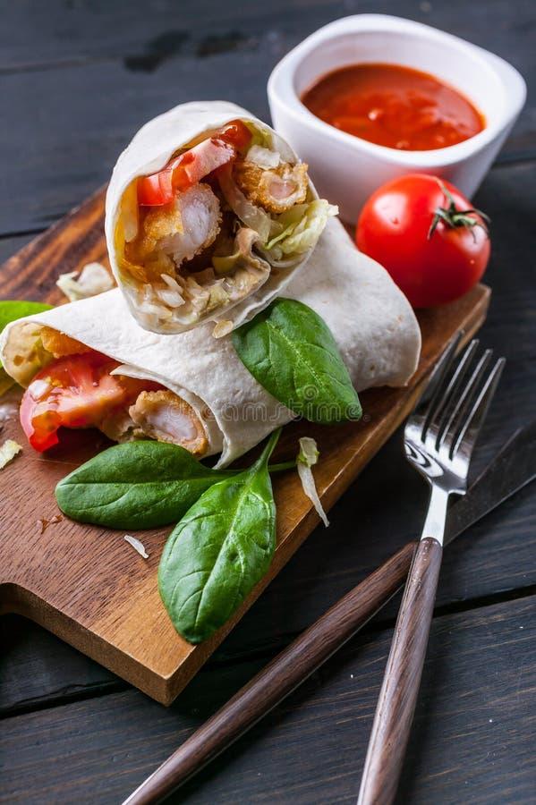 De omslagen van close-uptortilla's met gebraden garnalen, sla en tomaat op een houten scherpe raad Gezond voedsel Verticaal schot stock foto