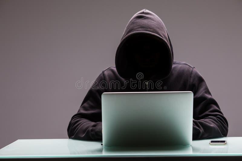 De onbekende Hakkersprogrammeur die computerlaptop voor houwer met behulp van informeert stock fotografie