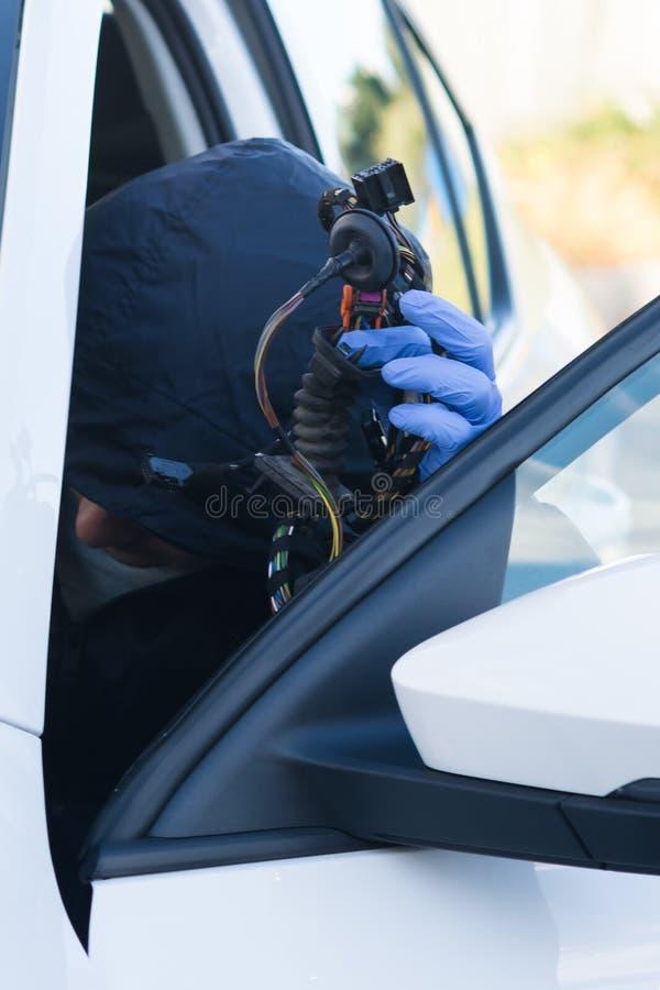 De onbekende persoon wil de computer aan boord van de auto binnendringen in een beveiligd computersysteem om het, close-up te kap royalty-vrije stock afbeelding