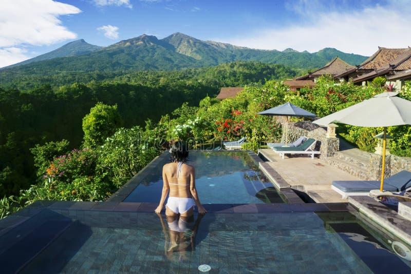 De onbekende vrouw geniet van mooi landschap in pool stock fotografie