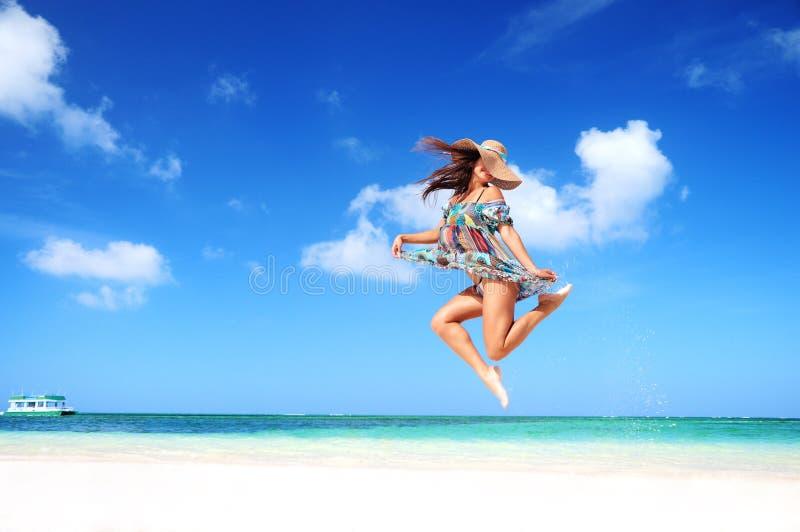 De onbezorgde jonge vrouw springt in de hemel stock foto's