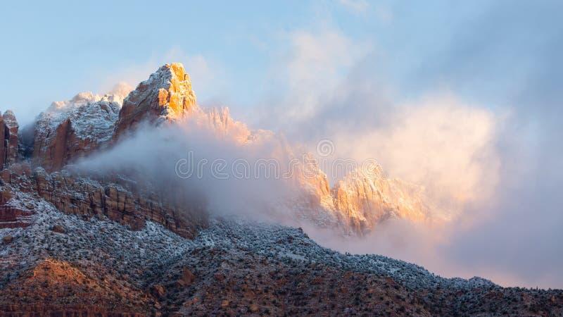 De onderbrekingen van de ochtendzon door de resterende sneeuwwolken en begint de lagere flanken van MT te raken Kinesava in Zuide royalty-vrije stock afbeeldingen