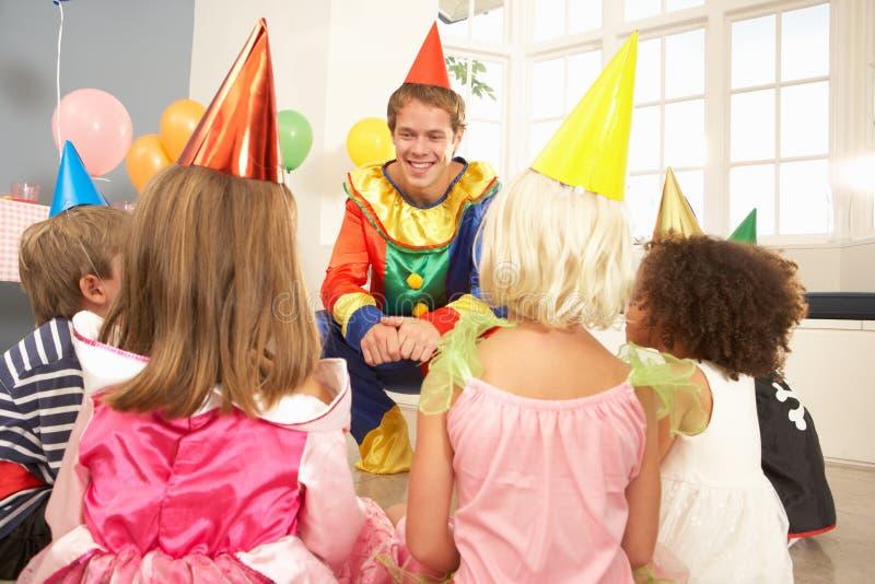 De onderhoudende kinderen van de clown bij partij royalty-vrije stock afbeeldingen