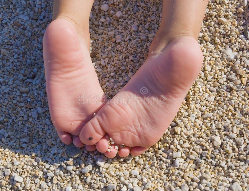 De onderkant die van hielenbaby op het strand ligt stock foto's