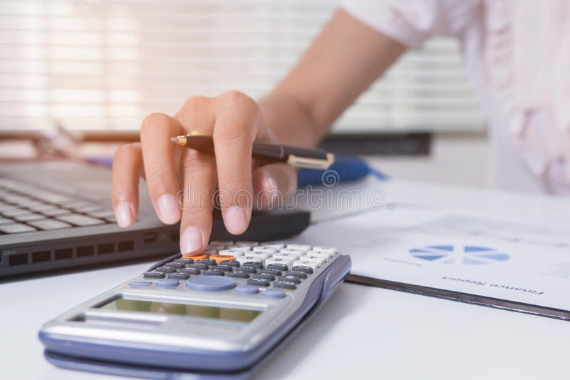 De onderneemster berekent over kosten en thuis doend financiënbureau, financier managerstaak, Conceptenzaken en investering royalty-vrije stock afbeeldingen