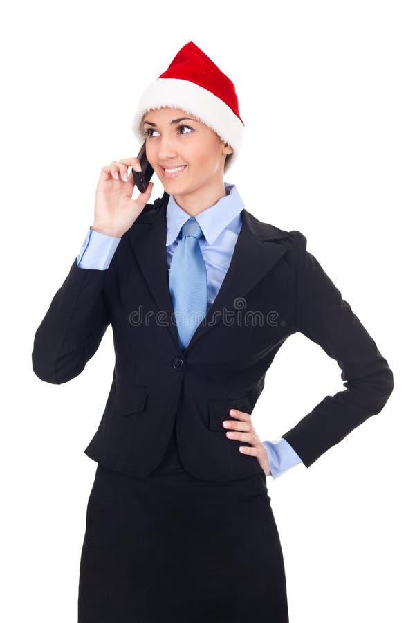 De onderneemster die van Kerstmis op telefoon spreekt stock afbeelding