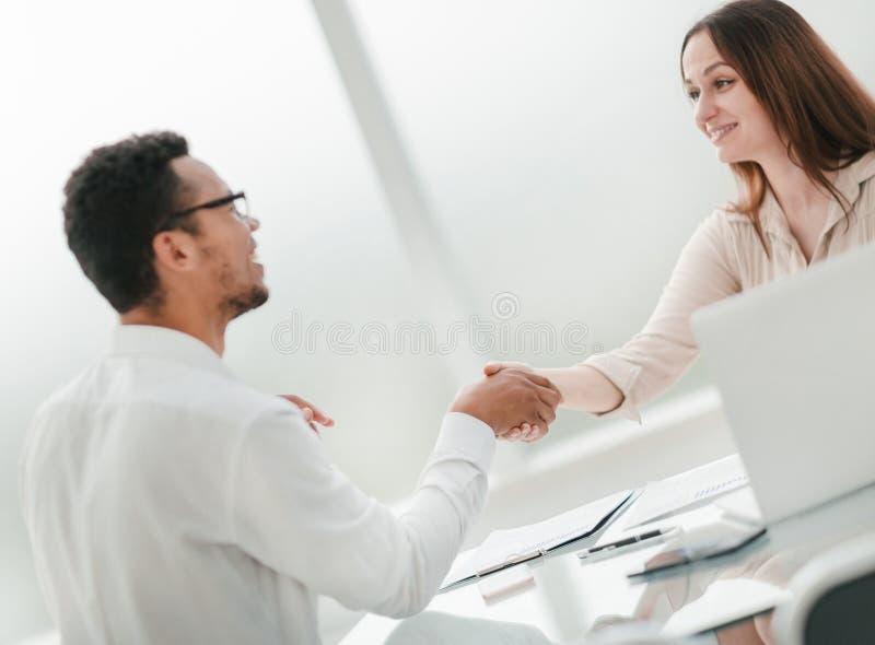 De onderneemster heet haar partner met een handdruk welkom stock foto