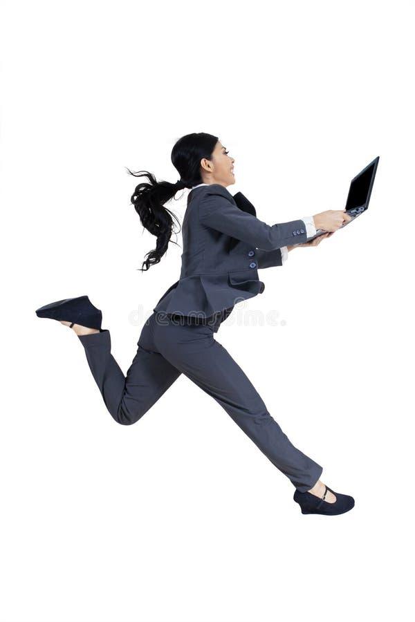 De onderneemster houdt laptop en loopt in studio stock foto