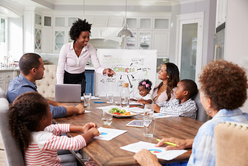 De onderneemster stelt vergadering aan een familie in hun keuken voor royalty-vrije stock foto