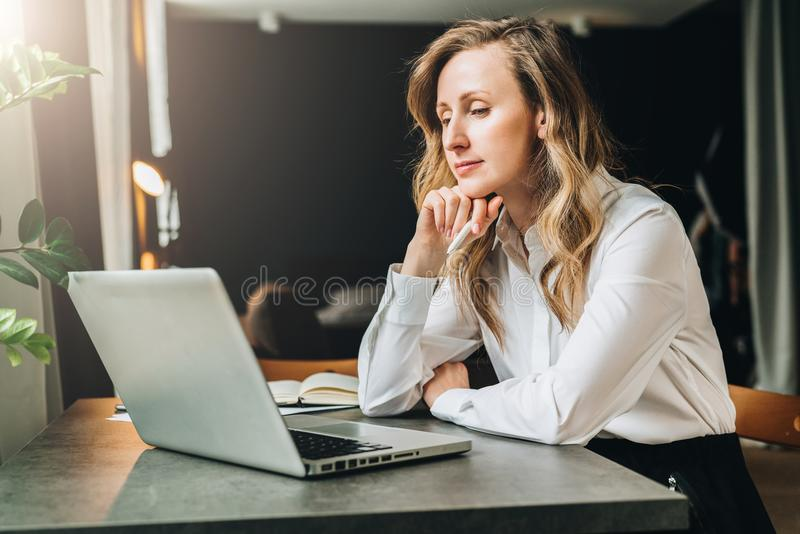 De onderneemster in wit overhemd zit in bureau bij lijst voor computer en bekijkt pensively het scherm van laptop royalty-vrije stock fotografie