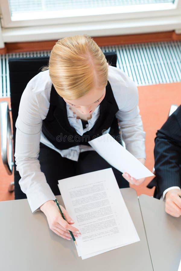 De onderneemster zit bij bureau stock foto