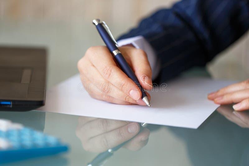 De onderneemsterhand schrijft op leeg document royalty-vrije stock afbeelding