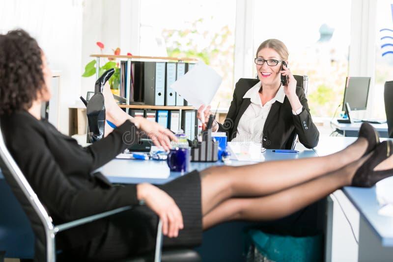 De onderneemsters ontspannen met hun voeten op het bureau op het werk stock fotografie
