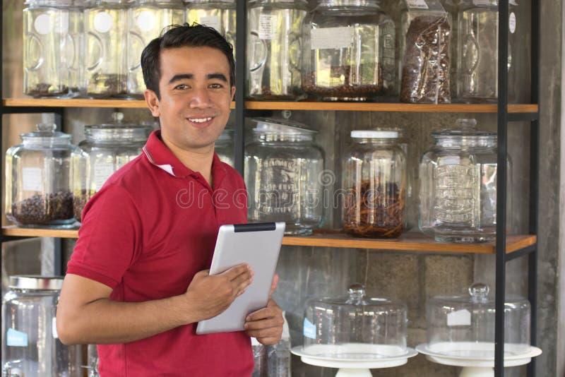 De ondernemers controleren voorraad op koffie in een kruikplank gebruikend tabletcomputer, zakenman die opslag controleren stock afbeeldingen