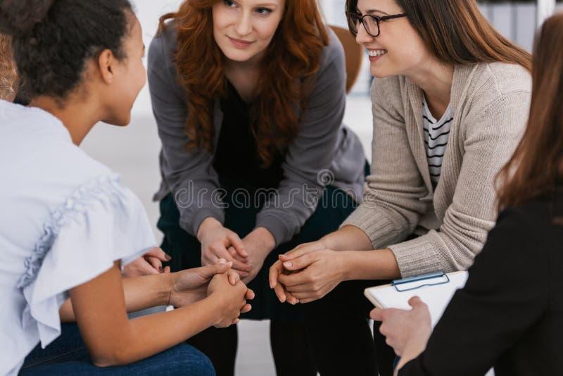 De ondersteunende vriend van de roodharigevrouw tijdens de vergadering van de psychotherapiegroep royalty-vrije stock afbeeldingen