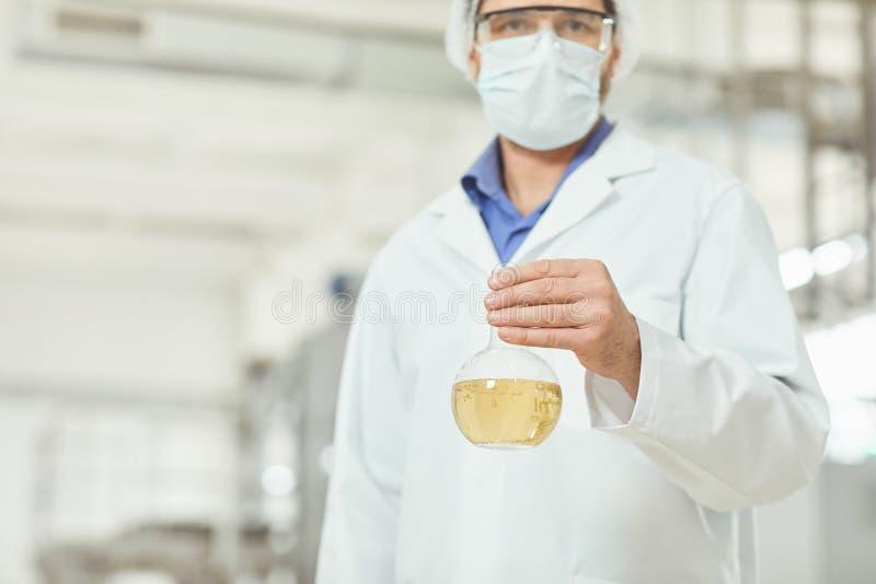 De onderzoeker is een man met een vloeistoffles in zijn handen tegen de achtergrond van de productie stock foto's