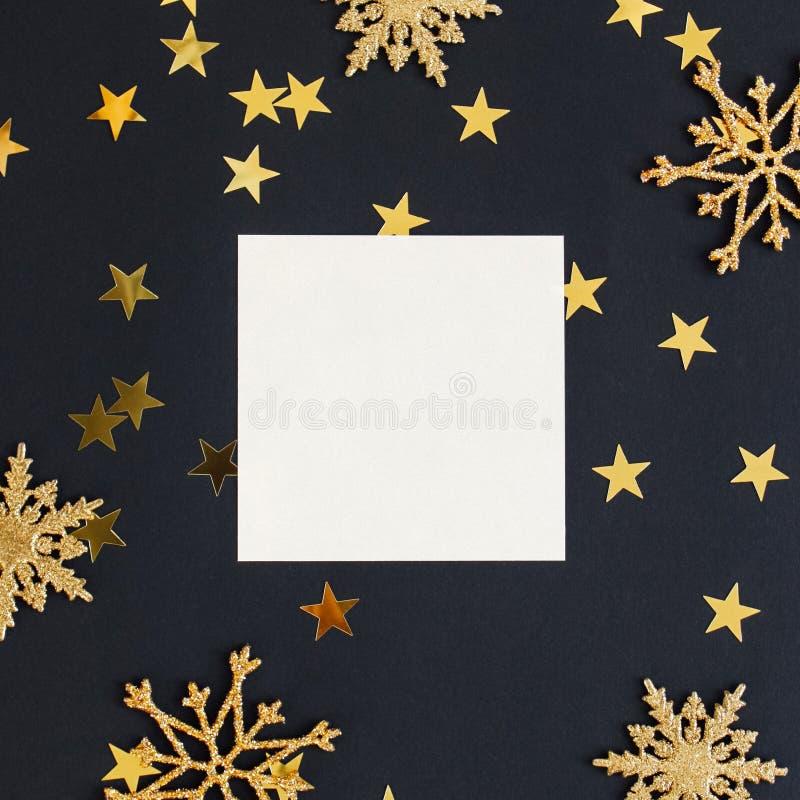 De onechte omhooggaande greeteng kaart op zwarte achtergrond met Kerstmisdecoratie schittert sneeuwvlokken en het goud speelt con stock fotografie