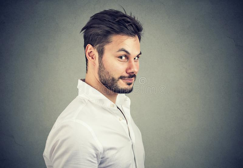 De oneerlijke mens die in wit overhemd kijken met beweert glimlach bij camera op grijze achtergrond royalty-vrije stock foto's