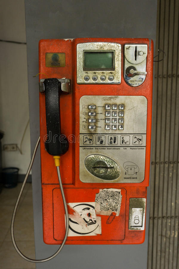 De ongebruikte die telefooncel hangt op de muurfoto in Djakarta Indonesië wordt genomen stock afbeeldingen