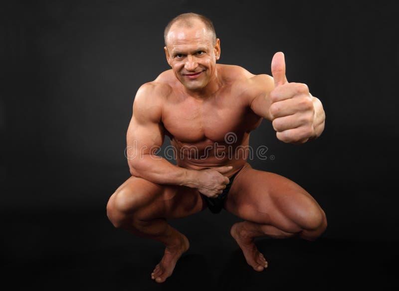 De ongeklede bodybuilder zit omhoog en beduimelt royalty-vrije stock foto's