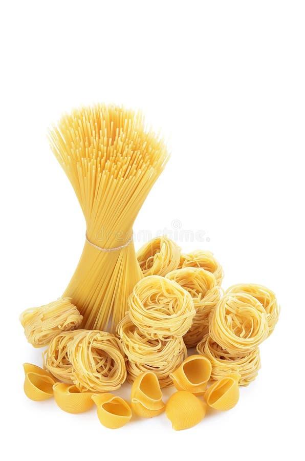 De ongekookte die macaroni van de deegwarenspaghetti op witte achtergrond wordt geïsoleerd stock foto's