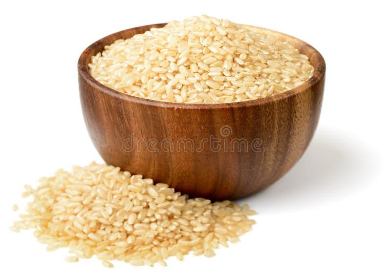 De ongekookte die ongepelde rijst in wooen kom, op de witte achtergrond wordt geïsoleerd stock afbeeldingen