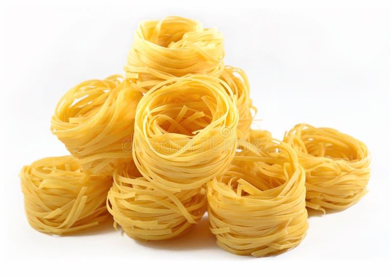 De ongekookte Italiaanse nesten van deegwarentagliatelle op een wit stock afbeeldingen