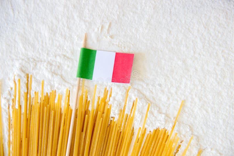 De ongekookte macaroni van de deegwarenspaghetti en de kleine Italiaanse vlag op wit floured achtergrond stock afbeelding