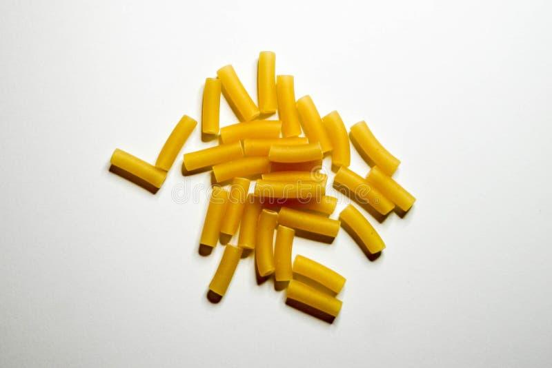 De ongekookte Ruwe gele stukken van Macaronideegwaren, in een gecentreerde hoop, in een witte studiospruit stock afbeeldingen