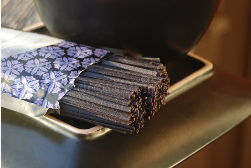 De ongekookte zwarte noedels van rijstsoba op een plaat stock fotografie